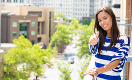 Beautiful woman relaxing on a balcony of her apartment on a summer day, giving a thumbs up Stock Images
