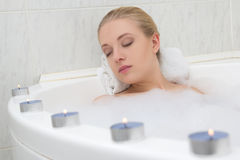 Beautiful woman relaxing in bath with candles Royalty Free Stock Photos