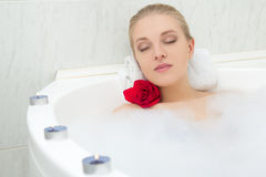 Beautiful woman relaxing in bath with flower and candles Stock Image