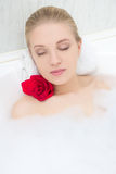 Beautiful woman relaxing in bath with red flower Stock Photo