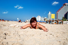 Beautiful woman relaxing on the beach. A woman sunbathing on the sand Royalty Free Stock Photo