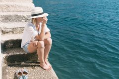 Beautiful woman relaxing on beach. Azure blue sea. Summer vacation. Straw hat. Young girl enjoys summer holiday. Stock Image
