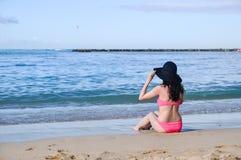 Beautiful woman relaxing on beach in Hawaii. A beautiful woman relaxing on the beach in Hawaii in her pink bikini and black sun hat Stock Photos