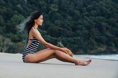 Beautiful woman relaxing on a beach with pineapple. Stock Images