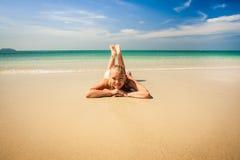 Beautiful woman relaxing on the beach. Beautiful young woman relaxing on the beach stock image
