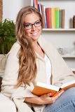 Beautiful woman relaxing with a book at home Royalty Free Stock Image