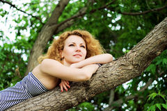 Beautiful woman is relaxing on a branch of tree Stock Photos