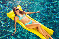 Beautiful Woman Relaxing Floating on Raft in Pool Royalty Free Stock Images