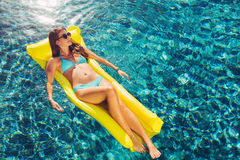 Beautiful Woman Relaxing Floating on Raft in Pool Royalty Free Stock Image