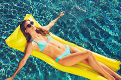 Beautiful Woman Relaxing Floating on Raft in Pool Stock Image