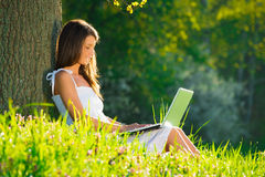 Beautiful  woman relaxing on grass with laptop Stock Photography