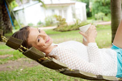 Beautiful woman relaxing on hammock with coffee. Side portrait of a beautiful woman relaxing on hammock with coffee cup Royalty Free Stock Photos