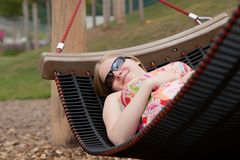 Beautiful woman relaxing in hammock in park Stock Image