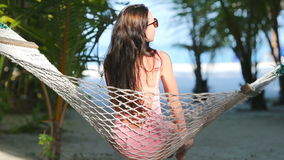 Beautiful woman relaxing at hammock on tropical beach. Beautiful woman relaxing at hammock on the tropical beach stock video footage