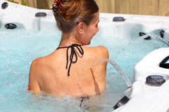 Beautiful woman relaxing in hot tub. Young beautiful woman relaxing in a hot tub royalty free stock images
