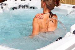 Beautiful woman relaxing in hot tub. Young beautiful woman relaxing in a hot tub royalty free stock photo