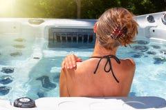 Beautiful woman relaxing in hot tub. Young beautiful woman relaxing in a hot tub stock photos