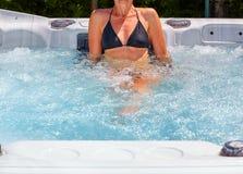 Beautiful woman relaxing in hot tub. Young beautiful woman relaxing in a hot tub stock photo