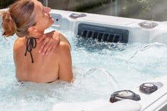 Beautiful woman relaxing in hot tub. Young beautiful woman relaxing in a hot tub stock photography
