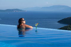Beautiful woman is relaxing in an infinity pool Royalty Free Stock Image