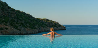 Beautiful woman relaxing in infinity swimming pool royalty free stock image