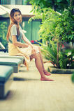 Beautiful woman relaxing on lounger near swimming pool in hotel, Royalty Free Stock Photography
