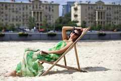 Beautiful woman relaxing lying on a sun lounger Stock Images