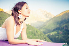 Beautiful woman relaxing and meditating outdoor at mountain Royalty Free Stock Image