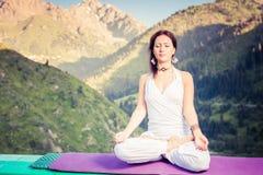 Beautiful woman relaxing and meditating outdoor at mountain Stock Photos