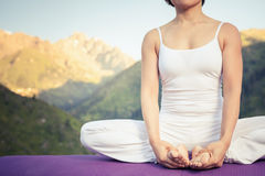 Beautiful woman relaxing and meditating outdoor at mountain Royalty Free Stock Images