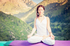 Beautiful woman relaxing and meditating outdoor at mountain Royalty Free Stock Photography