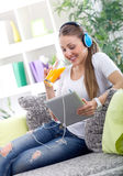 Beautiful woman relaxing with music and drink juice. Woman wearing headphones and  relaxing with digital tablet Royalty Free Stock Photos