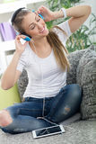 Beautiful woman relaxing with music. Woman wearing headphones and  relaxing with digital tablet Stock Photography