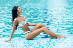 Beautiful woman relaxing near the pool Royalty Free Stock Photography