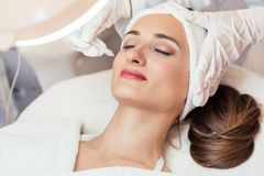 Beautiful woman relaxing during non-invasive facial treatment Royalty Free Stock Image