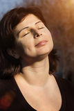 Beautiful woman is relaxing outdoor with closed eyes. Close up portrait of beautiful woman is smiling with closed eyes over sunlight, meditation outdoor Stock Photos