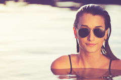 Beautiful Woman Relaxing in Pool at Sunset Stock Photos