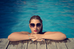 Beautiful woman relaxing at the poolside with wet hair wearing sunglasses. Lifted with her arms on the wood side of the pool Royalty Free Stock Photos