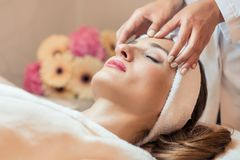 Beautiful woman relaxing during rejuvenating facial massage in a Royalty Free Stock Images