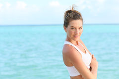 Beautiful woman relaxing by the sea after work out Royalty Free Stock Image