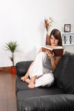 Beautiful woman relaxing on sofa reading a book Stock Photo