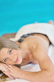 Beautiful woman relaxing in spa salon with hot stones on body. Beauty treatment therapy Stock Images