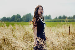 Beautiful woman relaxing and standing in yellow cornfield. Beautiful woman standing in yellow cornfield Stock Photography