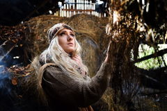 Beautiful woman relaxing in straw in autumn in smoky room Royalty Free Stock Image