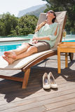 Beautiful woman relaxing on sun lounger by swimming pool Stock Images
