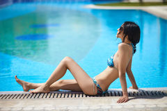 Beautiful woman relaxing and sunbathing near swimming pool Royalty Free Stock Photo