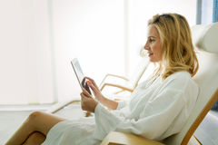 Beautiful woman relaxing and using tablet in spa Stock Images