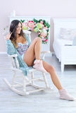 Beautiful woman relaxing in white rocking chair Stock Image