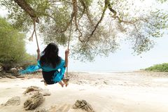 Beautiful woman relaxing on wooden swing under tree Stock Photos