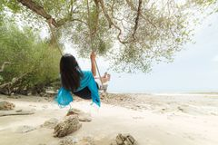 Beautiful woman relaxing on wooden swing under tree stock photography